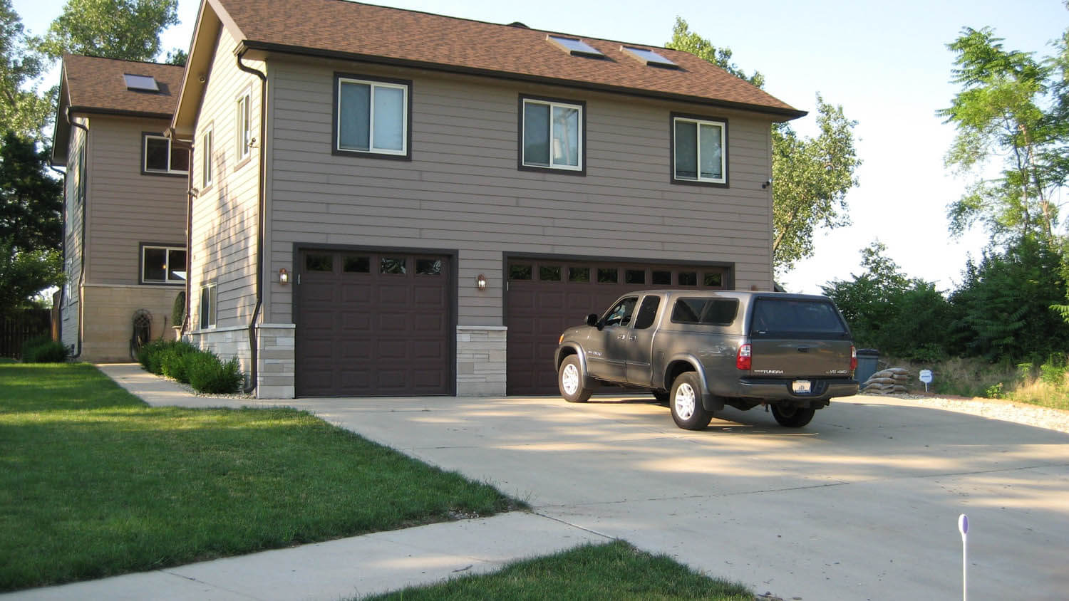 Outdoor view of a large home with a large drive way and a 3 car garage.