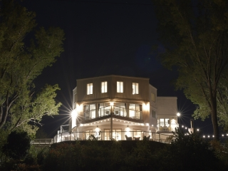 An nighttime outdoor view of the exterior of Villa Santorini, a large white vacation home with three levels. Surrounding the house is a stone patio with patio furniture and a fireplace.