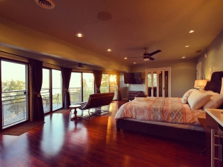 A king sized bed sits in a large bedroom. The bed faces toward a wall of large windows and patio doors that open to a small, Ship's Bow style deck. Outside you can see a small deck and views of Lake Michigan.
