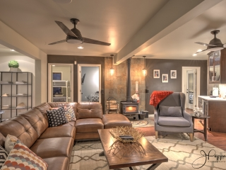 A large media room features a large brown leather sofa, a wooden coffee table, and a blue arm chair on top of a decorative rug. Beyond the seating area is a wood burning stove.