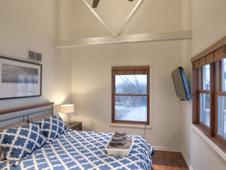 Interior view of a bedroom with a large bed with a matching comforter and pillows. The 16 ft ceilings feature large beams going across. A flat screen television hangs on the wall and windows reveal a view of the neighboring houses in the distance.