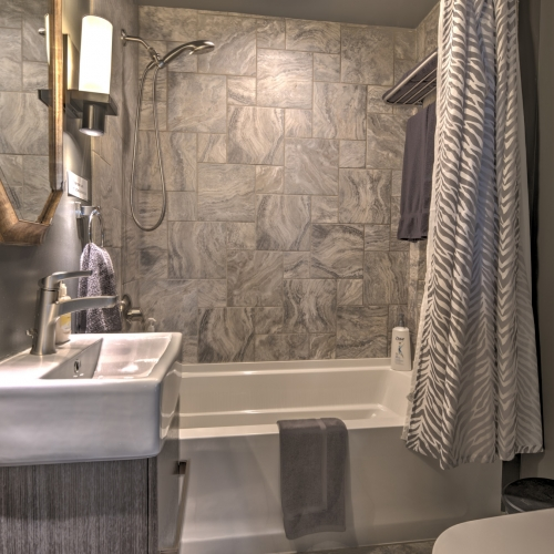 A bathroom with stone tile covering the floor and walls, to the left is a white sink atop a grey vanity.