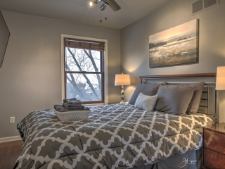 Interior view of a bedroom with a large bed with grey and white bedding. On each side of the bed is a wooden nightstand with a silver lamp on top. On the wall across from the bed is a large flatscreen television. From the window you can see trees.