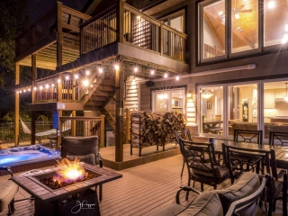 Multilevel outdoor patio at night with a table and chairs, a large hot tub, and a fire pit. You can see into the house through floor to ceiling windows.