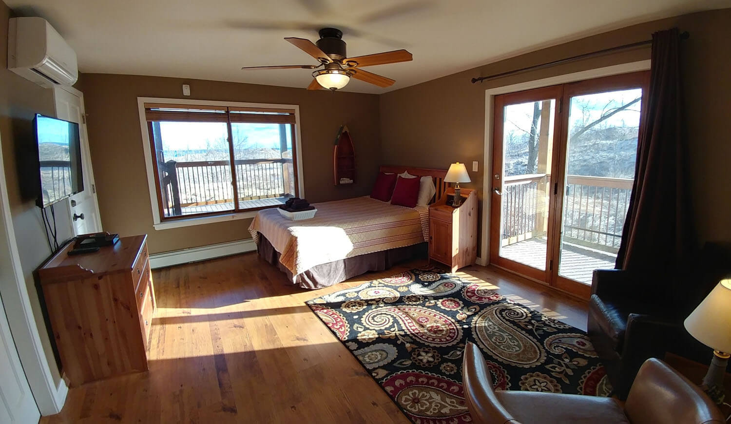 A large bedroom with wooden floors. A double bed sits in the corner across from an entertainment center with a large, flatscreen TV hanging on the wall. A sitting area with two leather armchairs and a side table sit on top of a decorative rug. Patio doors open onto the deck and the windows reveal views of the Indiana Dunes National Lakeshore.