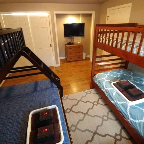 A bedroom with two sets of bunk beds sitting side by side. Across from the beds is a small nook with a small dresser and large flat screen TV hanging on the wall.