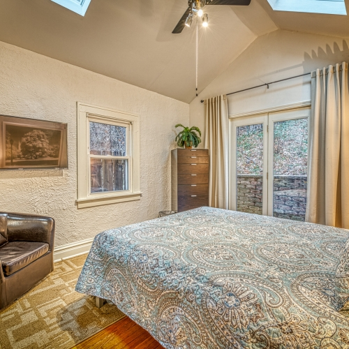 Bright skylighted queen bedroom with Smart TV and patio access
